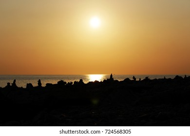 time of sunset on the Black Sea. Silhouette of pyramids of stones cairn on the shore. Orange soft color