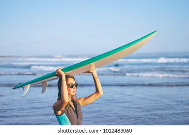 It's time for surfing! Hobby and vacation. Pretty young woman holding surf board on the sea beach.