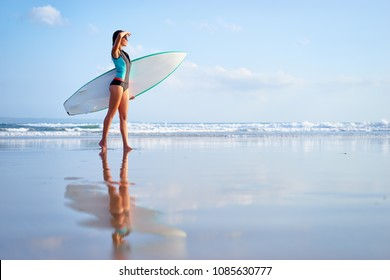 It's time for surfing! Hobby and vacation. Pretty young woman holding surf board on the sea shore.