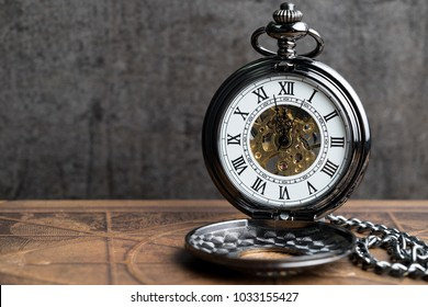 Time symbol or business deadline countdown concept, closed up vintage pocket watch on brown old book with black dark cement wall.