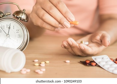 time to take medicine concept,woman hand taking pills with glass of water and clock on desk,