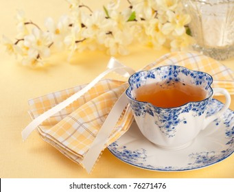 Time for Tea with Blue and White Vintage Teacup in Yellow Table Setting with flowers and room or space for copy, text, your words.  Square  looking down from above view at angle