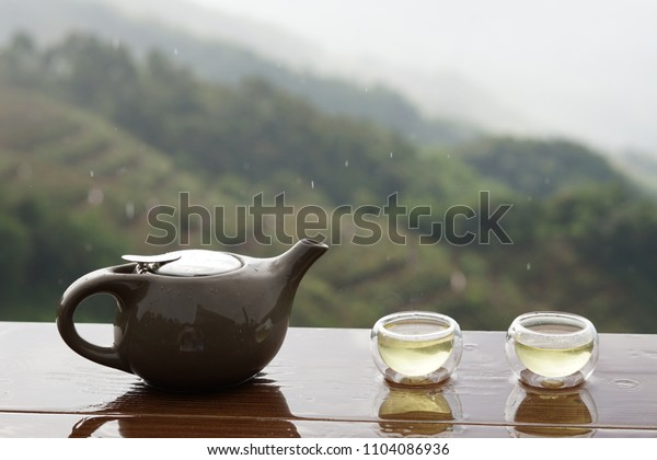 The Time of Tea Break. Teapot with cup set on the wooden table in front of mountain view and after rain, Traveling in Thailand.
