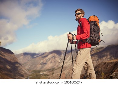 Time for thought. Handsome young bearded male hiker with sunglasses standing on the edge of a canyon looking into the distance