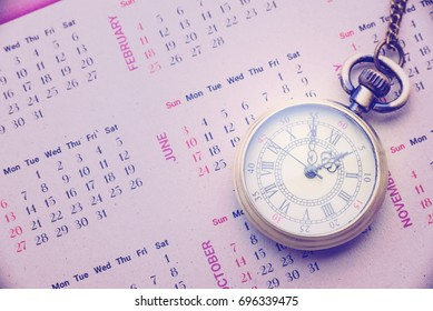 Time and tide wait for no man concept : Vintage brass pocket watch on a paper calendar, this image implies that people cannot stop the passing of time, and therefore should not delay doing things.