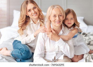 Time together. Joyful positive elderly woman smiling and feeling happy while spending time with her family