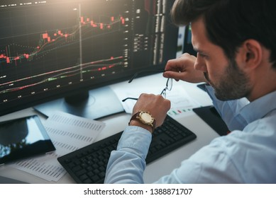 Time to trade. Bearded male trader looking at watch on his hand while working with data and charts on computer screens in his modern office.