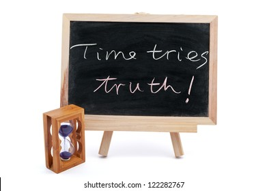 """""""Time tries truth"""" sayiings written on chalkboard with an hourglass beside it"""