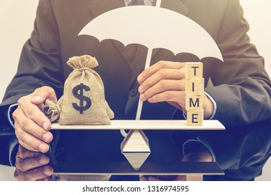 Time value of money, asset growth over time concept : Businessman protects or shields US dollar bags on a basic balance scale, depicts rising of present value when depositing or saving money in a bank