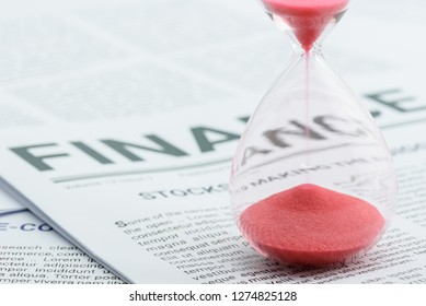 Time value of money, investment for sustainable wealth concept : Red sand clock, hourglass on a business printed media / daily report. Insight news update for long term investor to manage asset growth