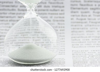 Time value of money, investment for sustainable wealth concept : White sand clock / hourglass timer on a business printed media / daily report. Insight news update for long term investor, asset growth
