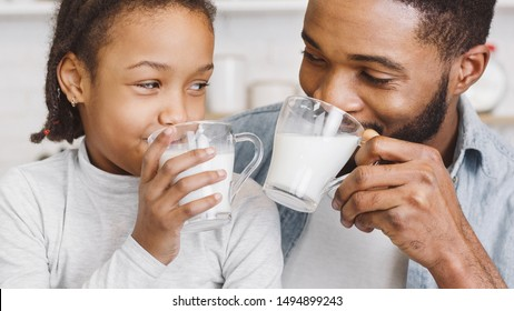 Time for vitamins. Cute Little African Girl And Her Handsome Dad Drinking Milk In Kitchen, watching each other