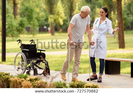 Time to walk in the park. A young female doctor helps the patient to walk on crutches, leaving his wheelchair behind.