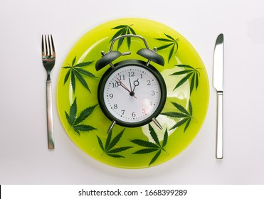 Time for Weed Pot Cannabis Clock Deadline Concept. Alarm clock Marijuana leaves around it on a light green plate with fork and knife Cutlery isolated on white gray background
