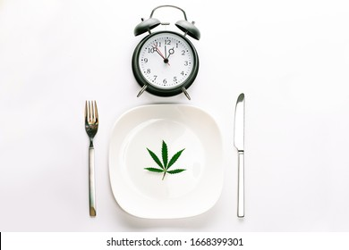 Time for Weed Pot Cannabis Clock Deadline Addiction Concept. Conceptual image of Alarm clock above a plate with a Marijuana leaf, fork and knife Cutlery around it isolated on white background