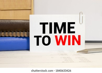 Time to win Blank album paper with time to win inscription on table with office items.