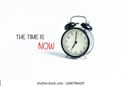 """""""THE TIME IS NOW"""" wordings with alarm clock against white background"""