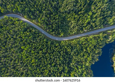 The time of year is summer. Road through a country of pine forests and lakes aerial view