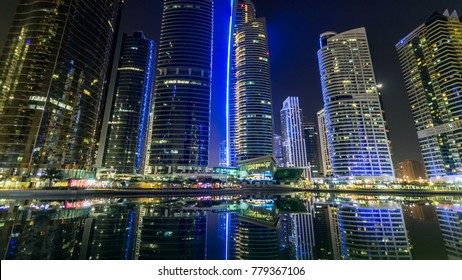 Timelapse  hyperlapse night view on illuminated skyscrapers at waterfront with palms. Residential buildings in Jumeirah Lake Towers in Dubai, UAE.  The JLT is a large development which consists of
