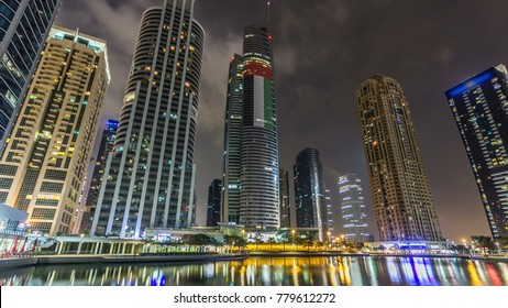 Timelapse hyperlapse night view on skyscrapers at waterfront with palms. Residential buildings in Jumeirah Lake Towers in Dubai, UAE.  The JLT is a large development which consists of 79 towers with