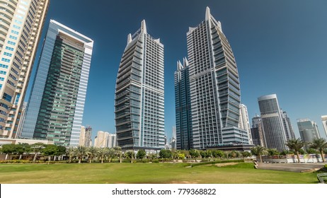 Timelapse hyperlapse view on skyscrapers at waterfront with palms. Residential buildings covered with glass in Jumeirah Lake Towers near park in Dubai, UAE.  The JLT is a large development whic