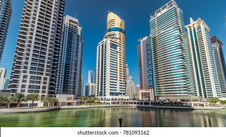 Timelapse hyperlapse view on skyscrapers at waterfront with palms. Residential buildings covered with glass in Jumeirah Lake Towers reflected in water in Dubai, UAE.  The JLT is a large developmen