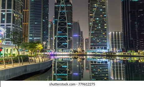 Timelapse night view on skyscrapers at waterfront with palms. Residential buildings in Jumeirah Lake Towers in Dubai, UAE.  The JLT is a large development which consists of 79 towers with 3 artificia