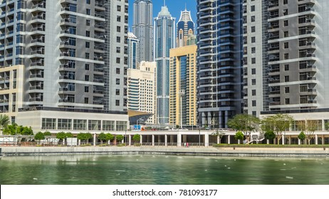 Timelapse view on skyscrapers at waterfront with palms. Residential buildings in Jumeirah Lake Towers with Dubai marina towers in backgroung in Dubai, UAE.  The JLT is a large development whic