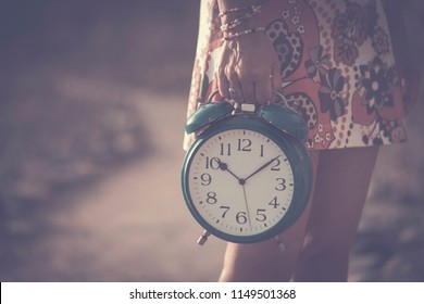 timeless and fairy concept. beautiful caucasian woman take an old big alarm. vintage colors and style. time and clock. one life to enjoy and to live