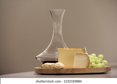 Timeline image for cheese and wine with friends gathering event or evening. The red wine is in a decanter. All products (cheese, bread and grapefruits) are on a wood plater.