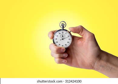 timer hold in hand, button pressed, yellow background