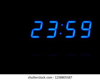Timer, minutes. Digital countdown at zero, blue figures on black blackground. Digital clock. Blue digital numbers indicate almost midnight.