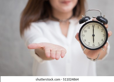 Times to pay the money bill or tax now, It's time to give me something concept, Asian women hand open palm and hold retro clock at 6 o'clock.