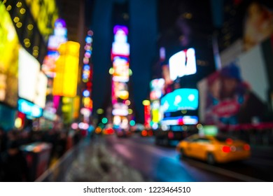 Times Square abstract defocus background night view of bright lights and traffic in wet winter street scene in New York City