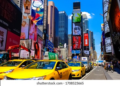Times Square with yellow New York City Taxi cabs and tour buses driving through colorful billboards. Manhattan, New York. USA - August 25, 2015.