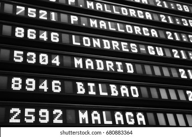Timetable at an airport in Spain. Flights to Mallorca, London, Madrid, Bilbao and Malaga. Black and white retro style.