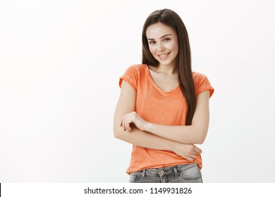 Timid cute girl asks for help. Portrait of insecure good-looking female in orange t-shirt, holding hands together on chest, smiling broadly and gazing at camera with friendly flirty expression