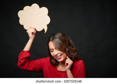 Timid smiling woman holding an empty thought bubble and looking down, over dark background