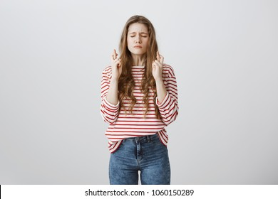 Timid and worried student praying for passing exams. Portrait of good-looking young european girl with tattoo closing eyes, focusing on wish, raising hands and crossing fingers, hoping over gray wall