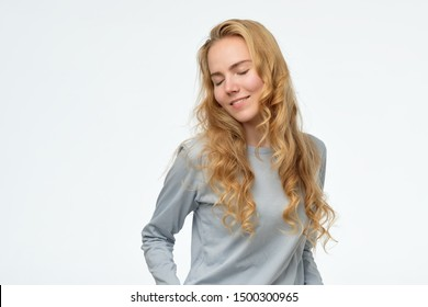 Timid young caucasian female looking down with shy smile, being embarrassed. Studio shot