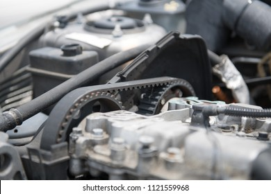 The timing belt of an automobile engine is visible on the side of the engine.
