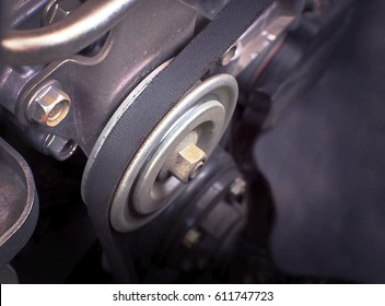 Timing belt and pulley in engine room of car.