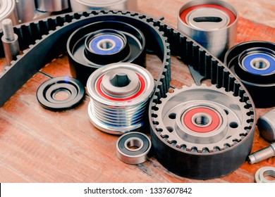 Timing belt pulley and pulley set that are placed on a wooden table in a car garage.Repair  car maintenance parts