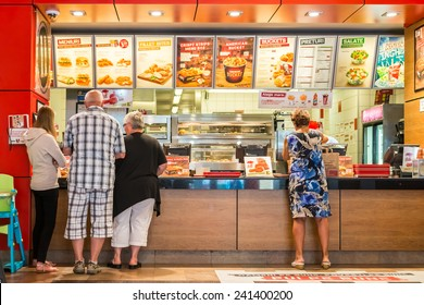 TIMISOARA, ROMANIA - AUGUST 25, 2014: People Order Kentucky Fried Chicken In Fast-Food Restaurant. It is a fast food restaurant chain headquartered in United States specialized in chicken products.