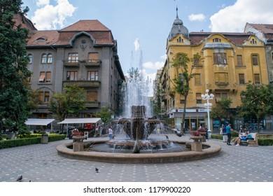 TIMISOARA, ROMANIA - CIRCA JULY 2017: Unidentified people walk past the fountain in Victory Square
