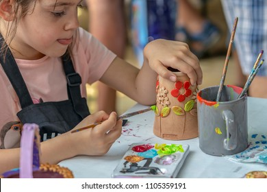 TIMISOARA; ROMANIA - JUNE 1; 2018: Little girl who paints ceramic funny objects. Workshop organized by the City Hall Timisoara with the occasion of the International children Day.
