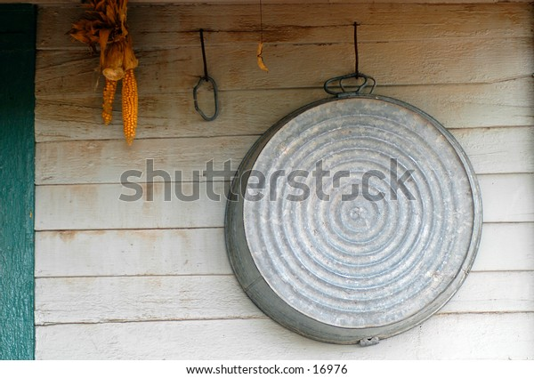 A tin bath hanging on wall with corn.