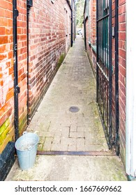 Tin Bucket in an Alleyway. with iron gate and brick walls