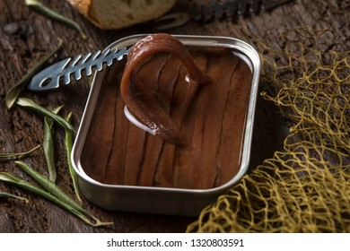 Tin can artisan anchovies from Cantabrian salting with olive oil on a rustic wooden table, close-up