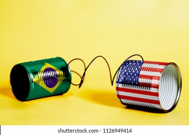 tin can phone with USA and Brazil Flag .communication concept on yellow